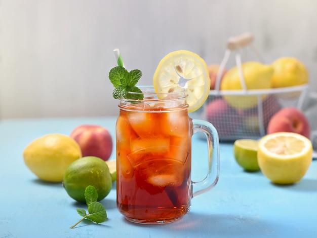 Tè freddo con limoni, lime e menta con cubetti di ghiaccio, bevanda estiva rinfrescante