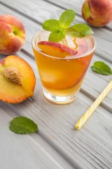 Tè freddo con pesche nel bicchiere sullo sfondo di legno grigio. posizione verticale.