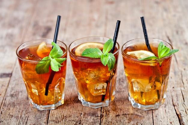 Tè freddo tradizionale con limone, foglie di menta e cubetti di ghiaccio in vetri sulla tavola di legno rustico.