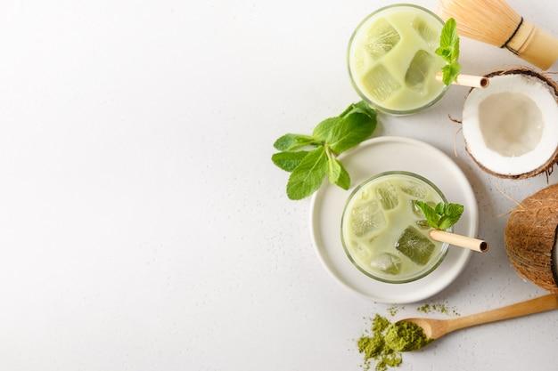 Tè ghiacciato di verde matcha del latte con la noce di cocco su fondo bianco. vista dall'alto