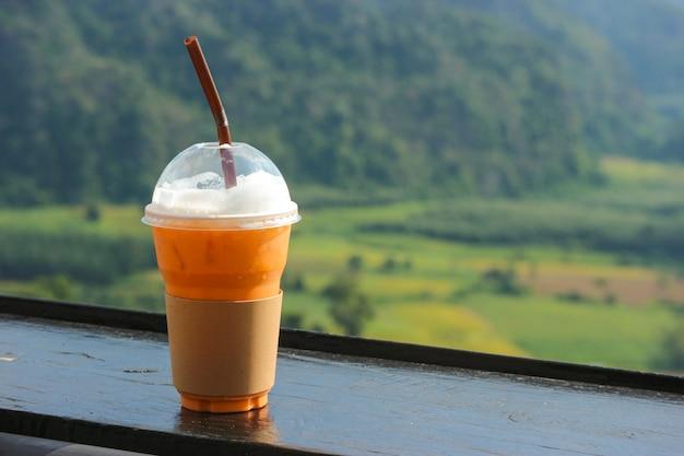 Tè ghiacciato tailandese in tazza di plastica con la vista natale come fondo.