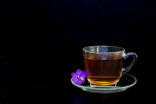 Tè in tazza di vetro con fiore orchidea pyrple isolato su bianco