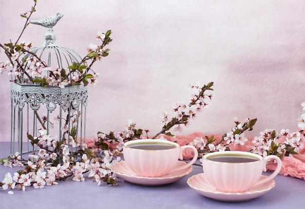 Tè in tazze rosa e fiori di ciliegio in una gabbia decorativa