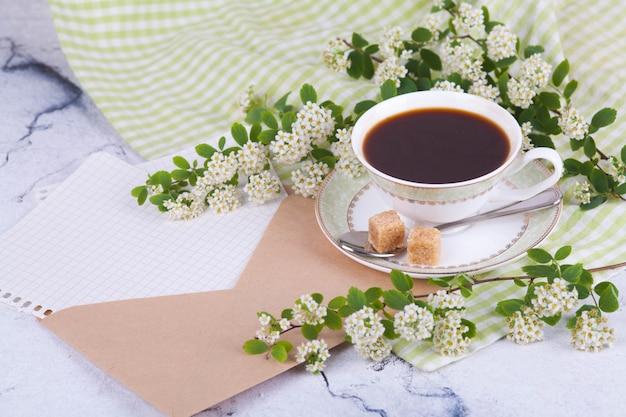 Tè in una bella tazza bianca. una busta di posta kraft con fogli di carta. prima colazione. un ramo di spirea fioriti. concetto giapponese wabi sabi