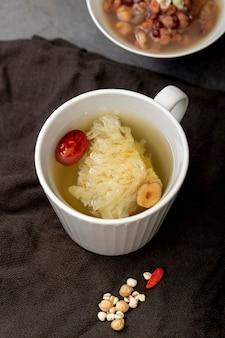 Tè in una tazza bianca e una ciotola con zuppa su un panno grigio