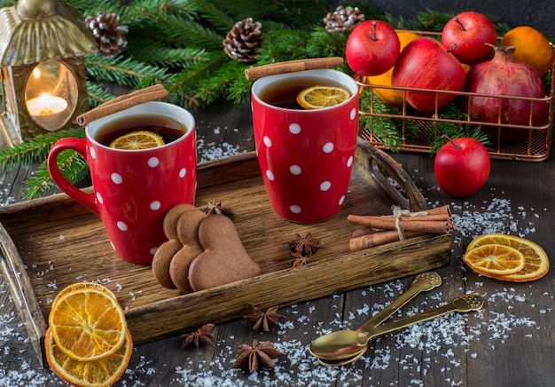 Tè in una tazza con una decorazione a maglia rossa, una lanterna, fette d'arancia, cesto di frutta, cannella, rami di abete e biscotti a forma di cuore