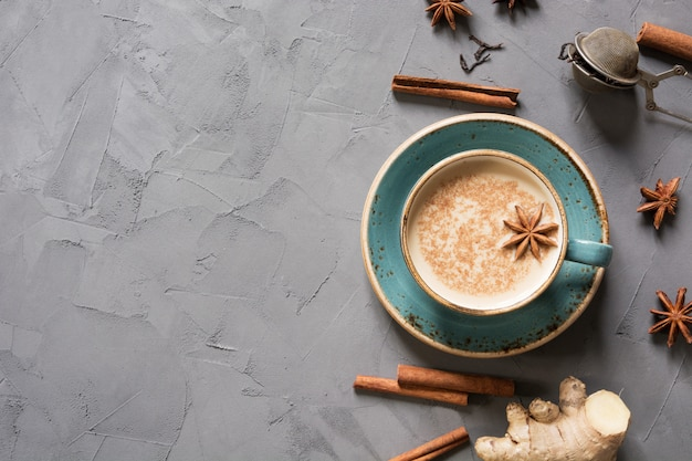 Tè indiano masala in tazza con spezie sul tavolo di cemento grigio. vista dall'alto.