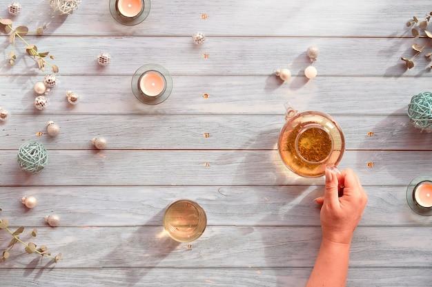 Tè invernale, disposizione con teiera in vetro, bicchiere di tè in mano. decorazioni natalizie: palline a specchio, palline, giocattoli, candele da tè ed eucalipto.