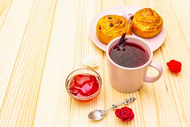 Tè karkade da petali di ibisco (rosa sudanese). dolce colazione romantica. panini, meringhe, gelatina di fragole. su una superficie di legno, copia spazio.