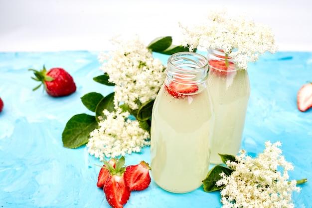 Tè kombucha con fiori di sambuco e fragola su sfondo blu.