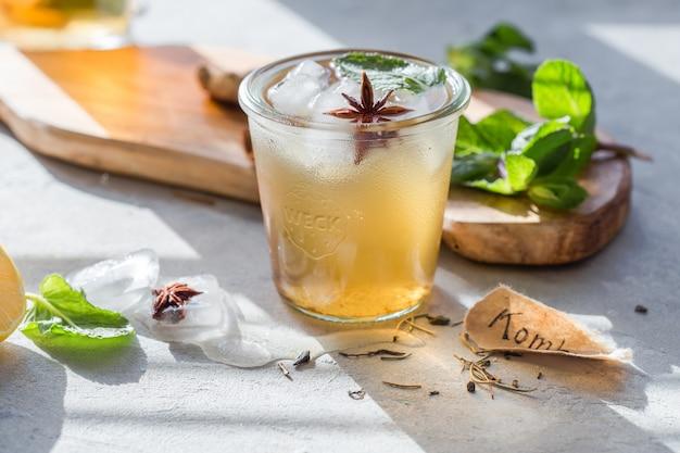 Tè kombucha o bevanda con tè freddo. super food fermentato, bevanda estiva pro biotic in vetro con menta, limone, su tavola di cemento