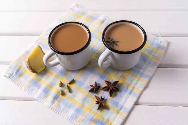 Tè masala chai in tazze di alluminio, spezie di anice sul tavolo bianco.