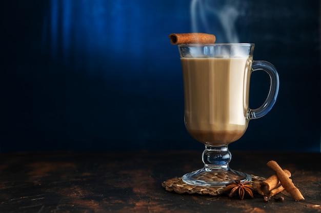 Tè masala con cannella e badian su un tavolo di argilla. un bicchiere di tè masala su sfondo blu.
