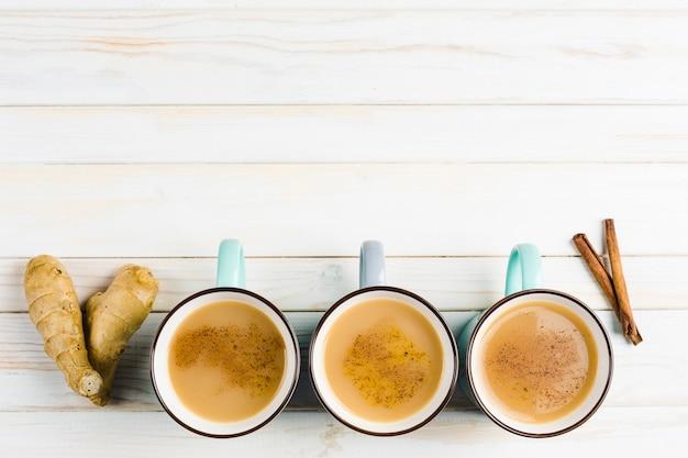 Tè masala in tazze di ceramica con spezie invernali di cannella e zenzero