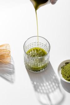 Tè matcha del primo piano che versa nel vetro