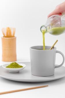 Tè matcha del primo piano che versa nella tazza