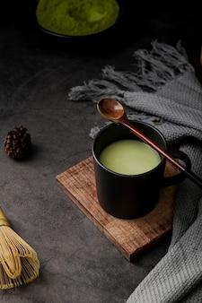 Tè matcha in tazza con cucchiaio e tessuto in legno