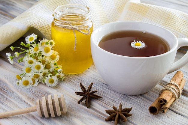 Tè, miele, cannella e camomille su legno