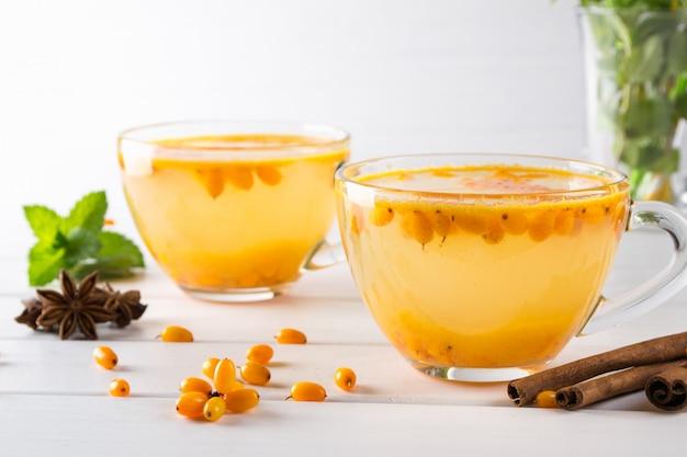 Tè naturale ai frutti di bosco con bacche fresche di olivello spinoso e bastoncini di cannella, stelle di anice