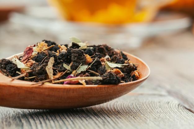 Tè nero con erbe in cucchiai di legno su una tavola di legno