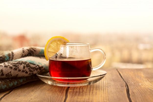 Tè nero con fette di limone in una tazza di vetro