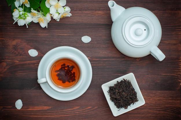 Tè nero con gelsomino in una tazza bianca su un tavolo di legno