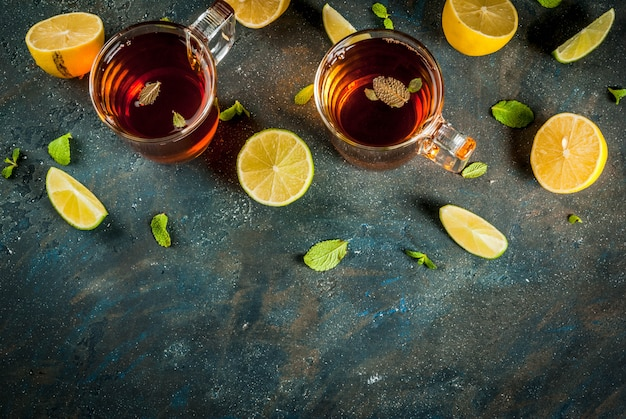 Tè nero con il limone e la menta sulla pietra concreta blu scuro, vista superiore del copyspace