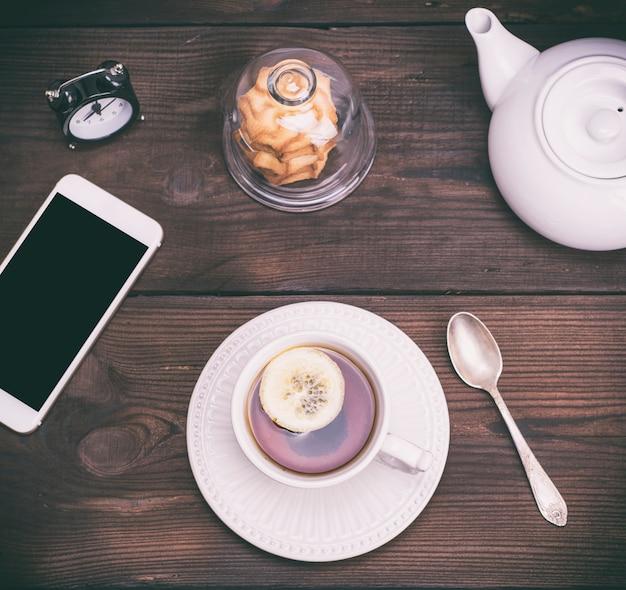 Tè nero con limone in una tazza di ceramica bianca rotonda