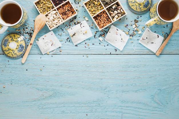 Tè nero fresco; varietà di erbe e bustina di tè disposti sul tavolo di legno