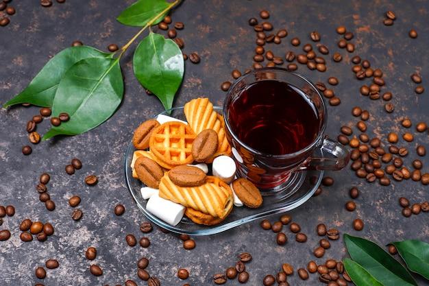 Tè nero in tazza di vetro con i dolci sul tavolo