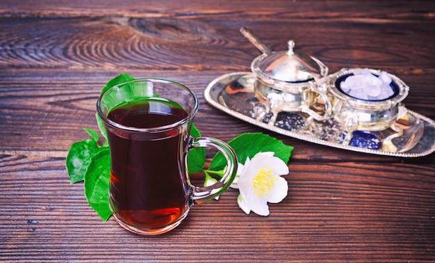 Tè nero in un bicchiere di vetro trasparente con manico