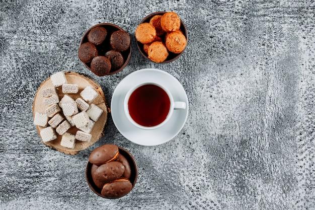 Tè piatto disteso in piatti con cialde e torte su texture leggera