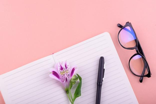 Tè profumato in una tazza bianca, bellissimi fiori, un quaderno con penna e occhiali.