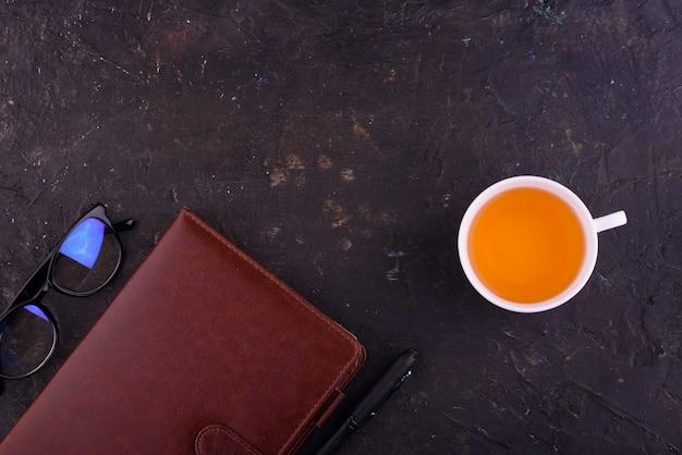 Tè profumato in una tazza bianca, un quaderno con una penna e occhiali.