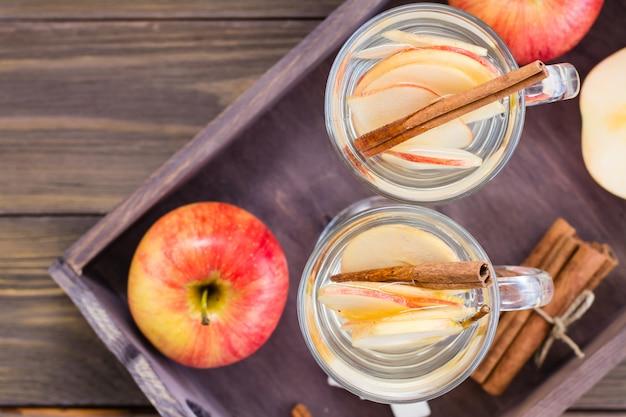 Tè rilassante alla mela e cannella in bicchieri su un tavolo di legno. disintossicante, antidepressivo. stile rustico. vista dall'alto