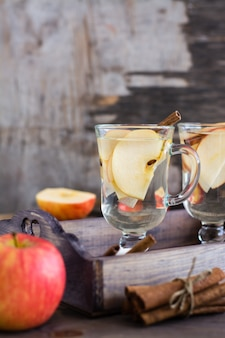 Tè rilassante alla mela e cannella in bicchieri su un tavolo di legno. disintossicante, antidepressivo.