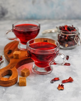 Tè rovente dell'ibisco in una tazza di vetro su calcestruzzo con i petali asciutti dell'ibisco