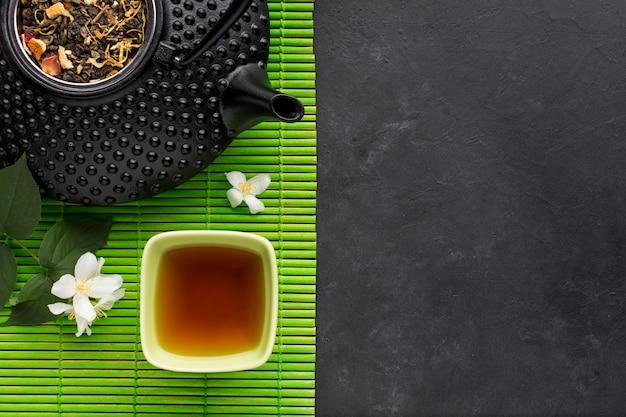 Tè sano con erbe secche e fiori di gelsomino bianchi su tovaglietta verde su sfondo nero