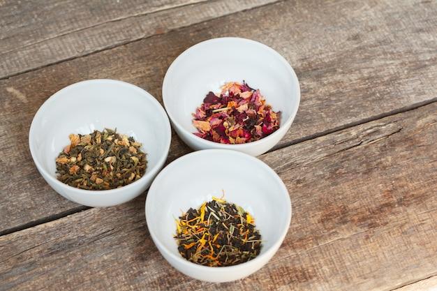 Tè secco aromatico in ciotole su legno