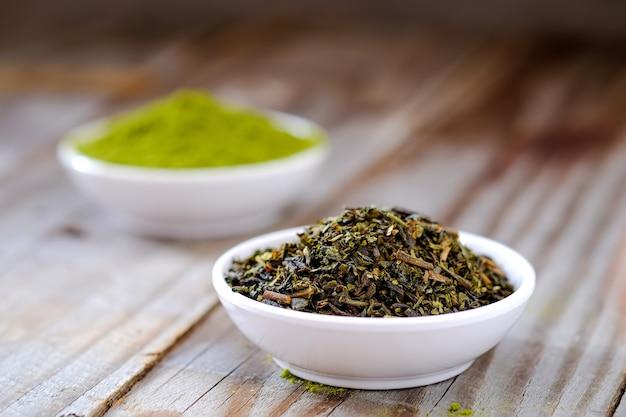 Tè secco con polvere di tè verde in tazza bianca.