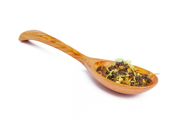 Tè secco su un cucchiaio di legno, isolato su bianco