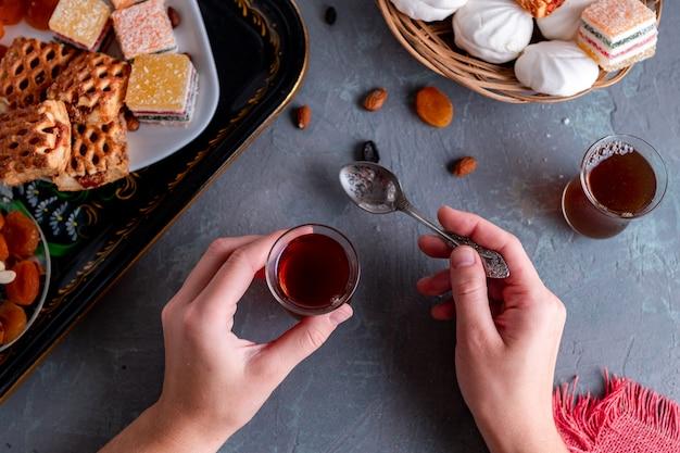 Tè turco in vetro tradizionale con dolci, frutta secca e noci per l'ora del the. vista dall'alto
