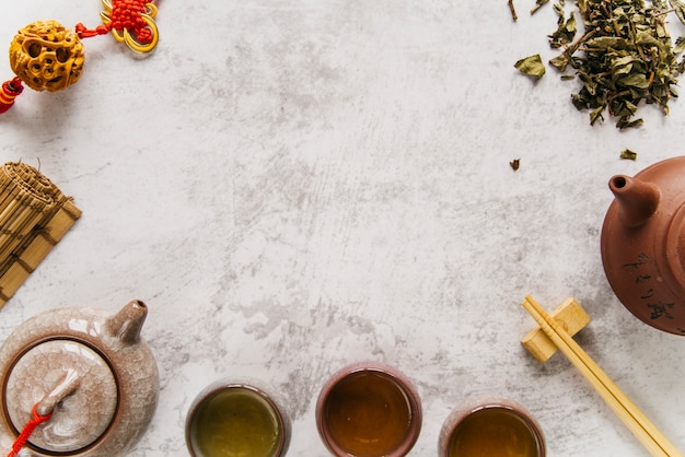 Tè verde caldo in due tazze di ceramica tradizionale cinese e teiera in ceramica con fiocco