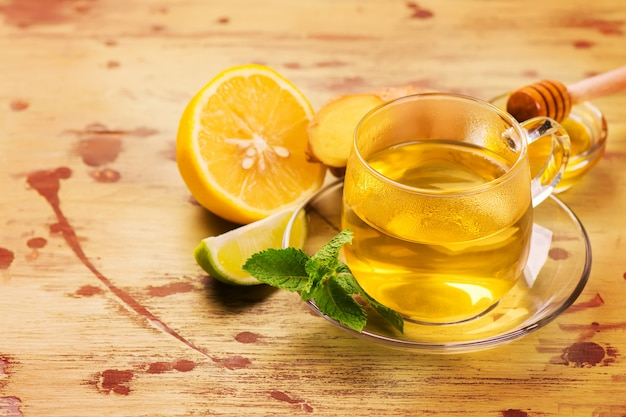 Tè verde caldo in una tazza di vetro servito con limone, zenzero, lime, miele e menta
