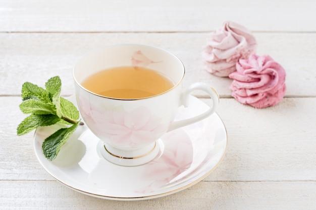 Tè verde con menta e marshmallows su fondo di legno bianco