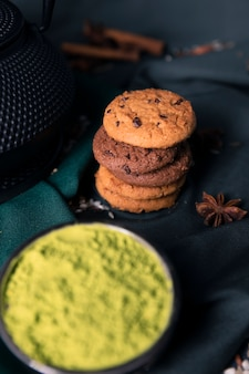 Tè verde della polvere di vista del primo piano con i biscotti