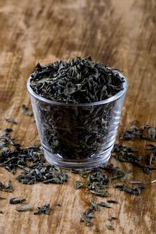 Tè verde di alta qualità in primo piano di vetro su fondo di legno