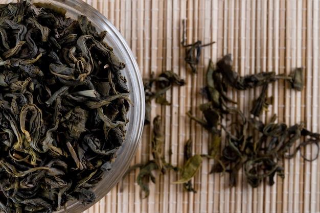 Tè verde di alta qualità in primo piano di vetro sul fondo della paglia