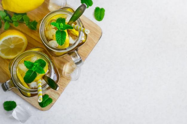 Tè verde freddo con limone e menta in un barattolo di vetro.