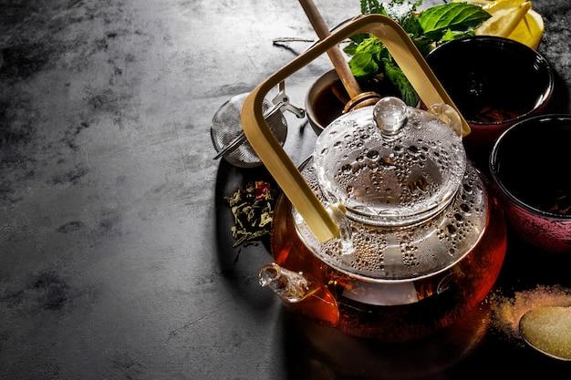 Tè verde fresco gustoso nella ceramica di teiera di vetro su sfondo scuro sopra